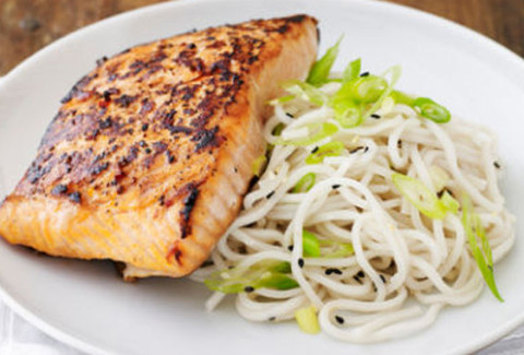 Pan seared crispy salmon drizzled with teriyaki sauce and served with sesame soy lo mein noodles and vegetables