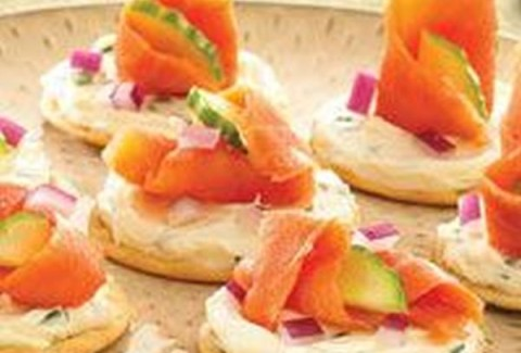 Smoked salmon roulade made with herbed cream cheese, sliced and served on a cracker.